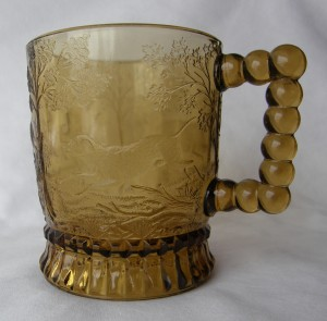 """Dog Chasing Deer (Size: 3-1/4"""" dia. x 3-3/4"""" ht.; Color: Amber) To the left of the handle, sculpting shows a dog chasing the deer shown further around the bowl of the mug."""
