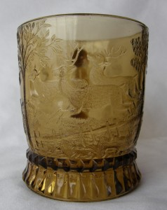 """Dog Chasing Deer (Size: 3-1/4"""" dia. x 3-3/4"""" ht.; Color: Amber) Directly opposite the handle, sculpting shows a doe and two stags running from the dog further around the bowl of the mug."""