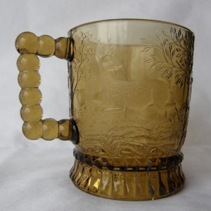 """Dog Chasing Deer (Size: 3-1/4"""" dia. x 3-3/4"""" ht.; Color: Amber) To the right of the handle, sculpting shows a young stag looking back over its left shoulder."""