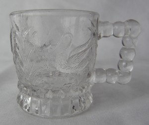 """Swan - aka Water Fowl, U.S. Glass No. 3802, or Federal's No. 3802 (Size: 1-7/8"""" dia. x 2"""" ht.; Color: Clear) To the left of the handle, sculpting shows a swimming swan among cattails."""