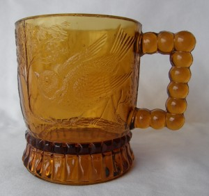 """Bird on a Branch (Size: 2-7/8"""" dia. x 3-3/8"""" ht.; Color: Amber) To the left of the handle, the sculpting shows a crouching song bird perched on a branch."""