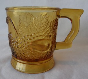 """Strawberry & Pear; handle at right; pear side showing (size: 3"""" diameter x 3-3/8"""" height; color: amber)"""