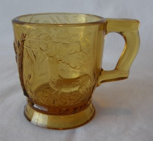 """Feeding Deer and Dog; handle at right (size: 2-3/8"""" diameter x 2-5/8"""" height; color: amber)"""